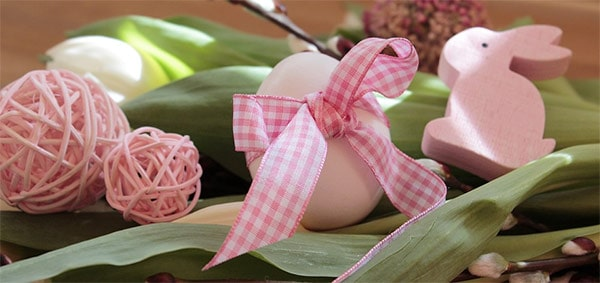 Pastel pink Easter egg tied with gingham ribbon, and a pale pink bunny rabbit on green leaves
