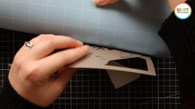 Silver card coming away from a blue Cricut mat