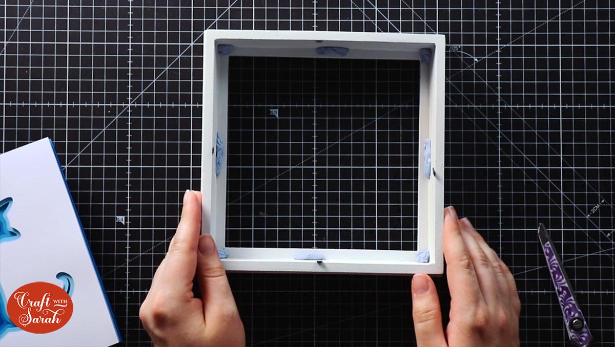 Add blu tak to the frame to add space